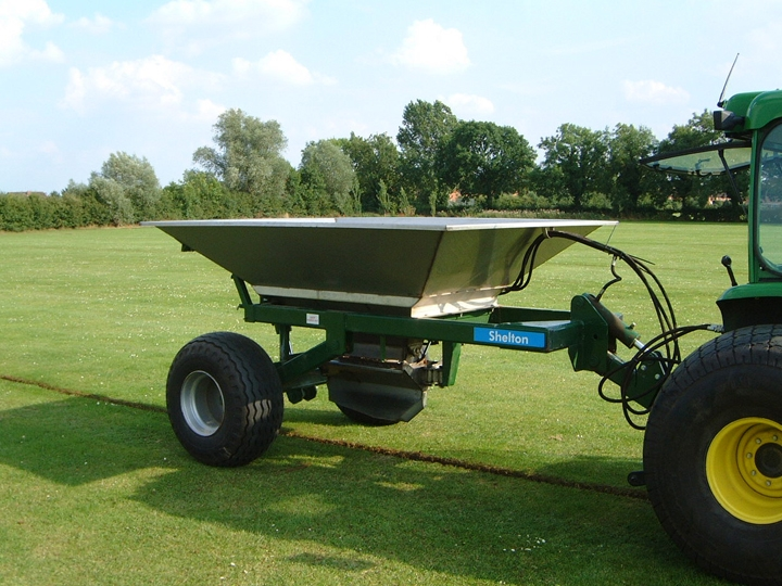 Shelton 3 tonne fast flow gravel hopper hitched to tractor side view